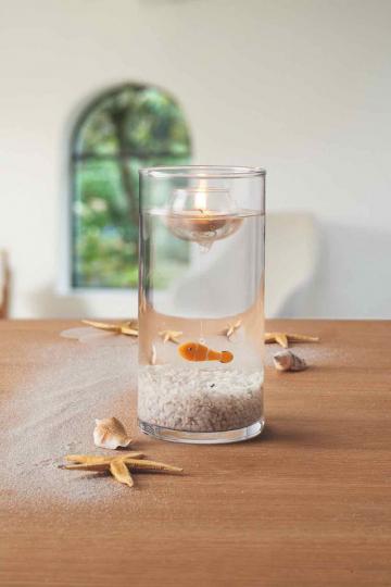 Glasvase mit Fisch und Schwimmlicht.